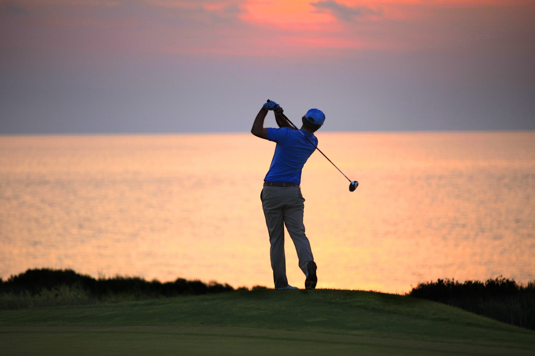 golf-player-swings-bat-while-enjoying-the-sunset-in-golf-course